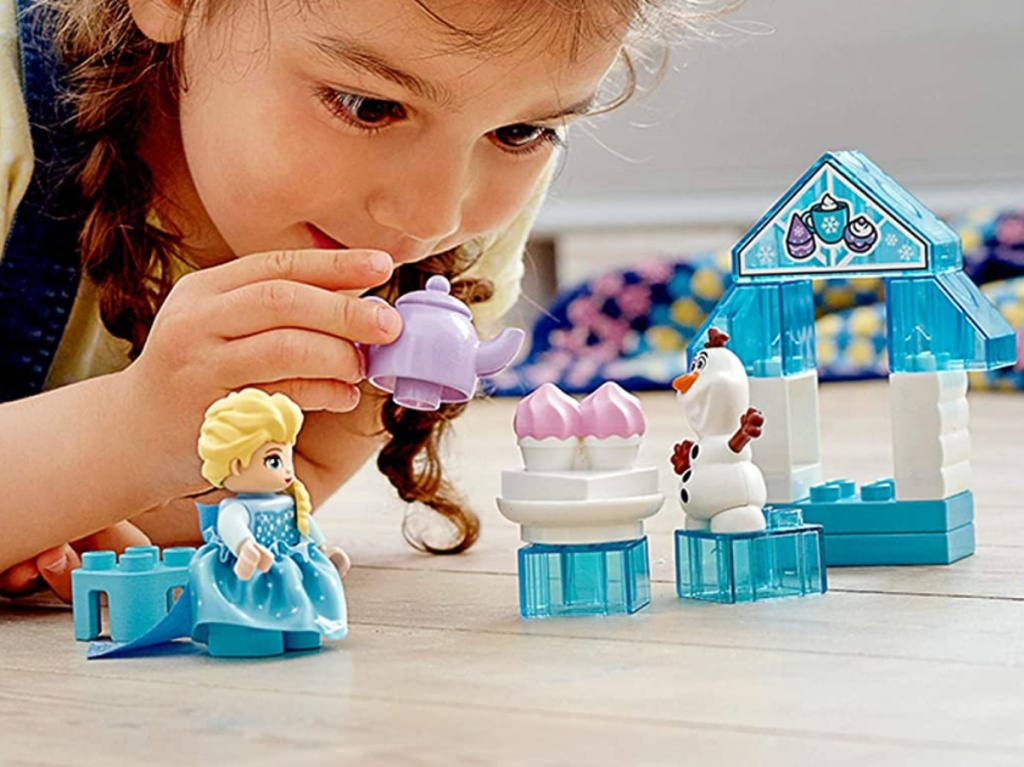 young girl playing with Disney LEGO toy set