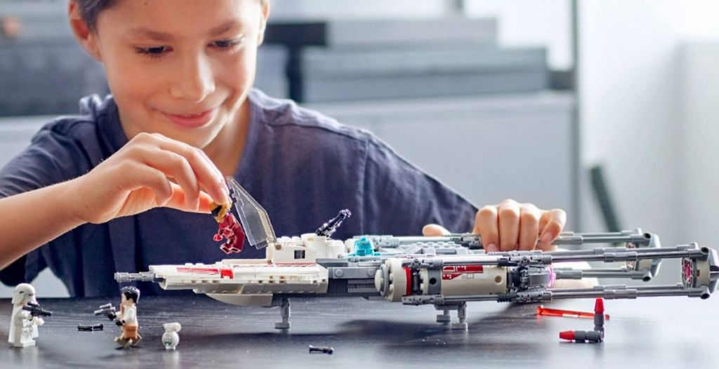 kid playing with LEGO ship