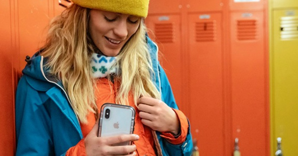 woman holding a phone standing by lockers
