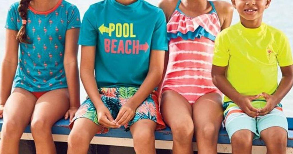 four children sitting on a bench wearing Lands End Swimwear