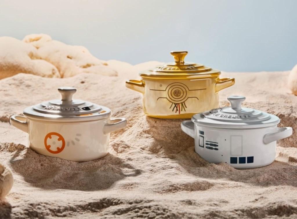 three Le Creuset Star Wars Mini Cocotte on sand like a planet