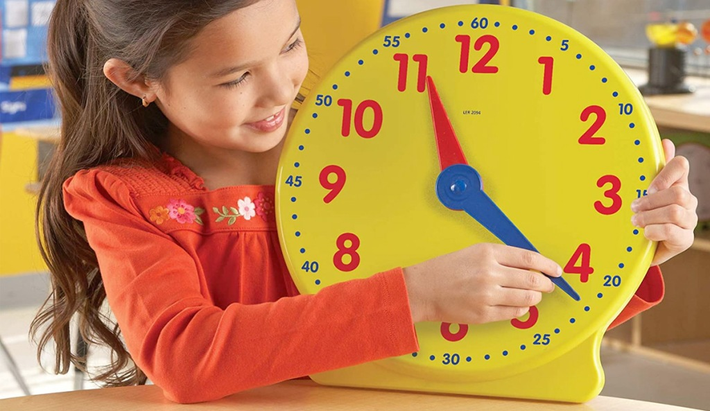 girl playing with large yellow plastic clock with red numbers and red & bluehands