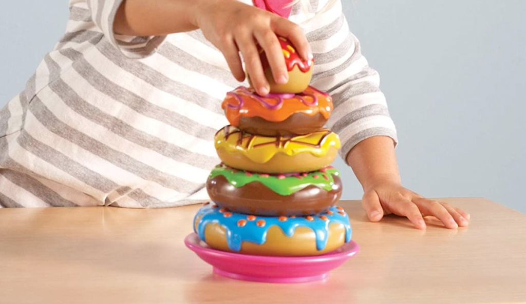 child playing multi-colored doughnut stacking game