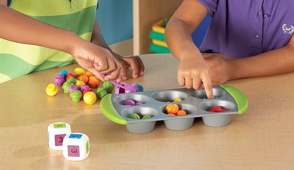 kids sorting small toys into cups of a muffin tin