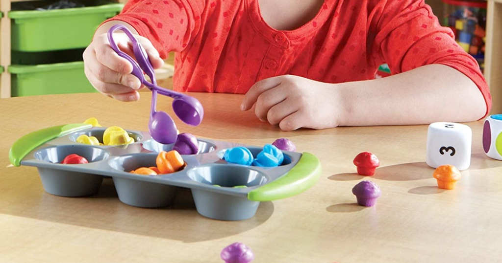 child using pair of purple plastic tongs to sort our small toys into cups of a muffin tin