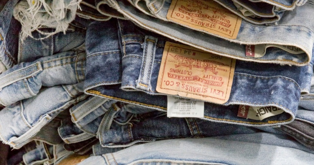 pile of levis jeans in different washes