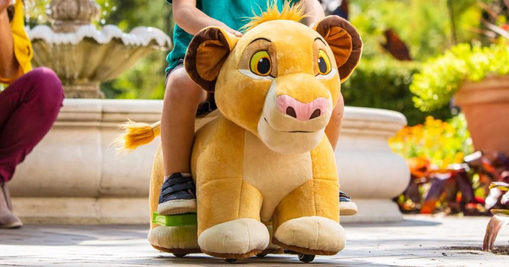 child riding on a lion king simba shaped plush ride-on toy