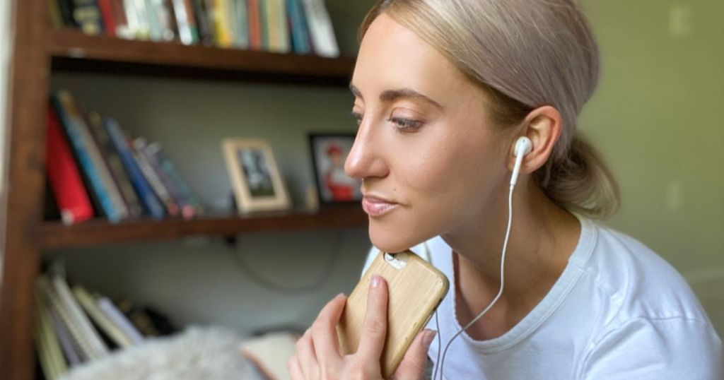 Woman holding iphone and listening to a podcast with headphones in