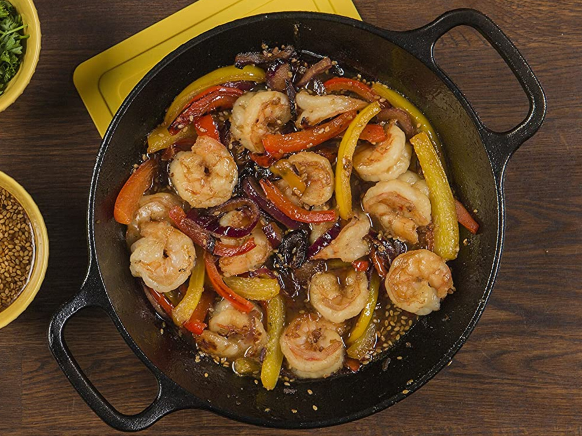 shrimp and veggies in black cast iron pan on wood table with bowls of seasoning
