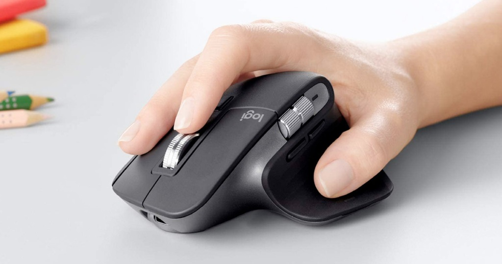 persons hand resting on top of a black wireless mouse