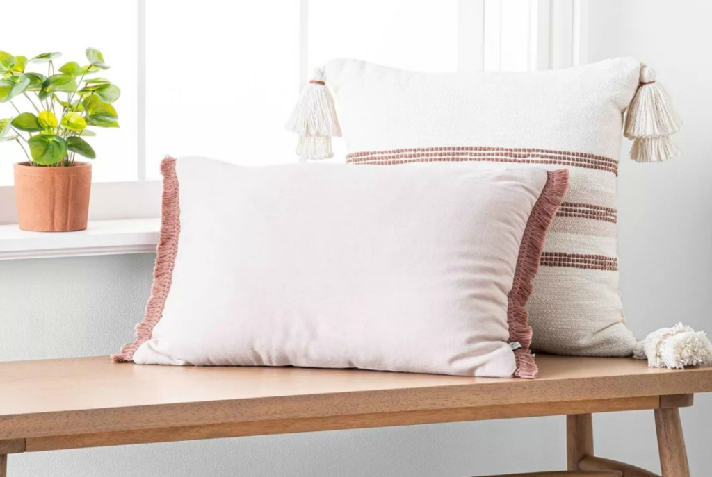 Rose colored throw pillow on a bench