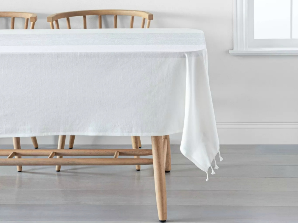 Wooden dining with white striped table cloth and coordinating chairs