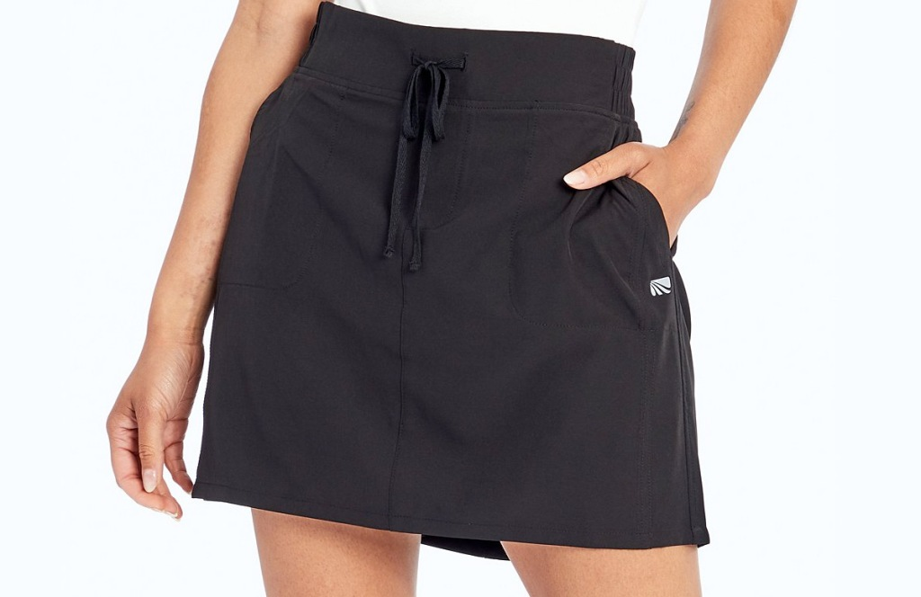 woman wearing black skort with pockets and tie at waist
