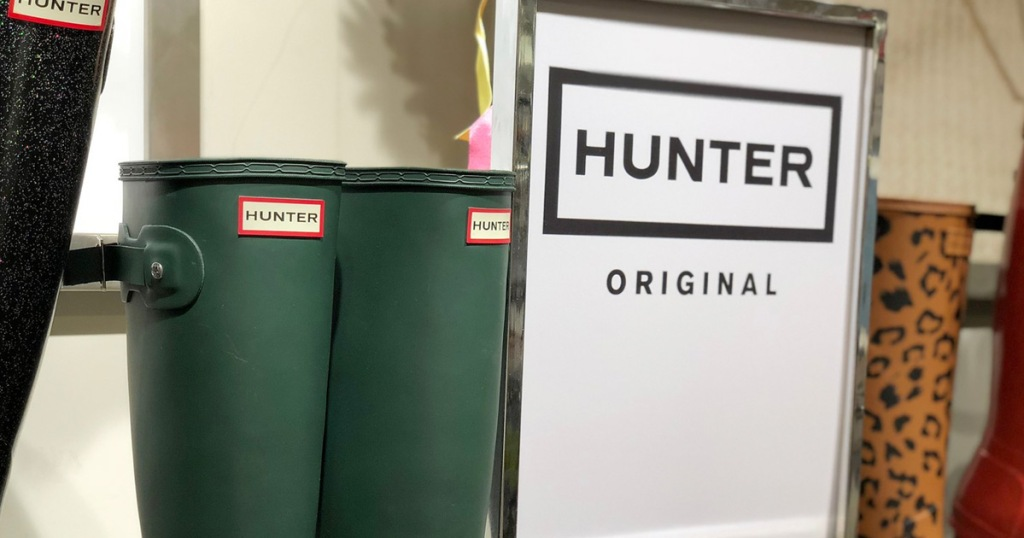 pair of matte green hunter brand rain boots next to store display sign for hunter brand
