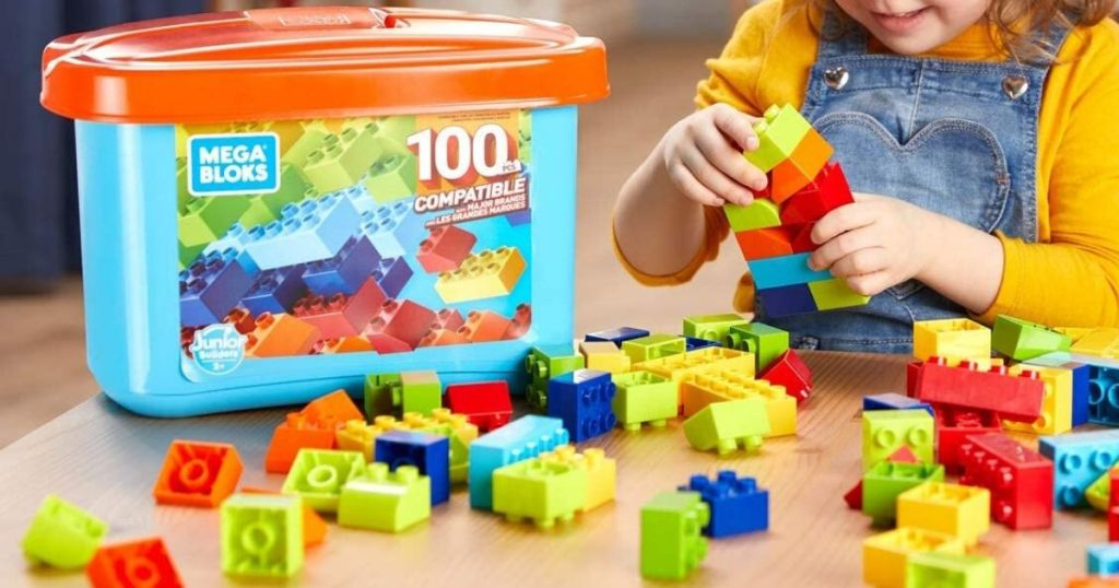 little girl playing with chunky style blocks at table with pieces spread out in front of storage bin