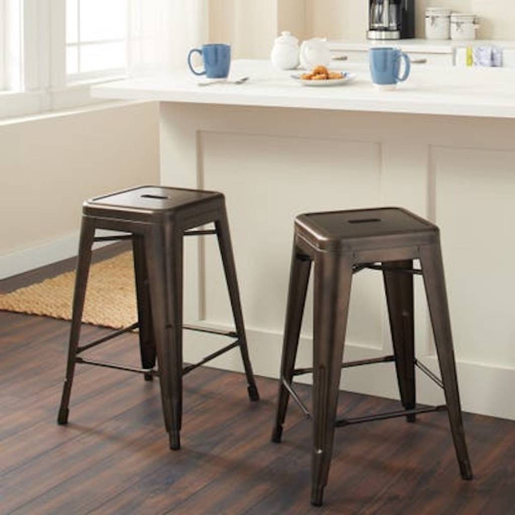two metal bar stools in gunmetal under kitchen counter top with two blue coffee cups
