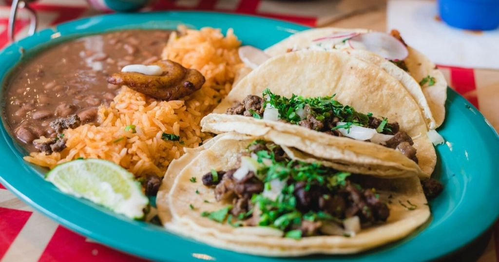 plate of mexican tacos with rice and refried beans