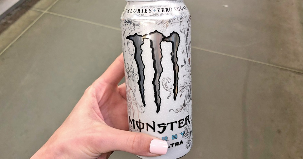 girl with light pink nails holding white can of monster energy drink
