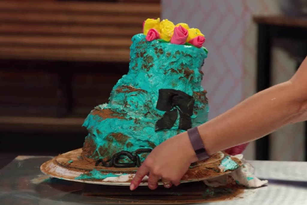 hands placing blue tiered cake on table