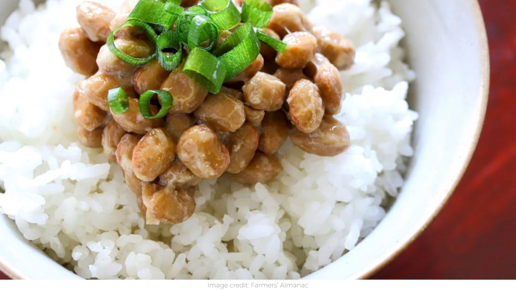 close up photo of natto and chives over white rice in bowl