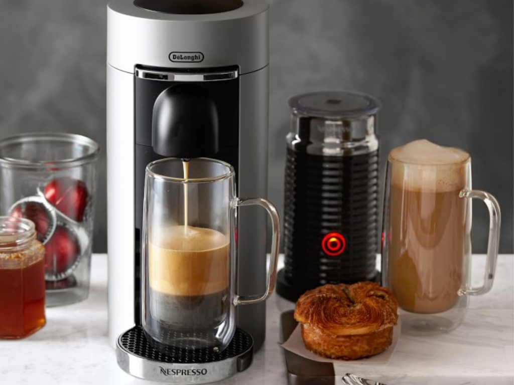 Nespresso VertuoPlus Deluxe Coffee Maker & Espresso Machine by De'Longhi brewing coffee into glass cup with muffin