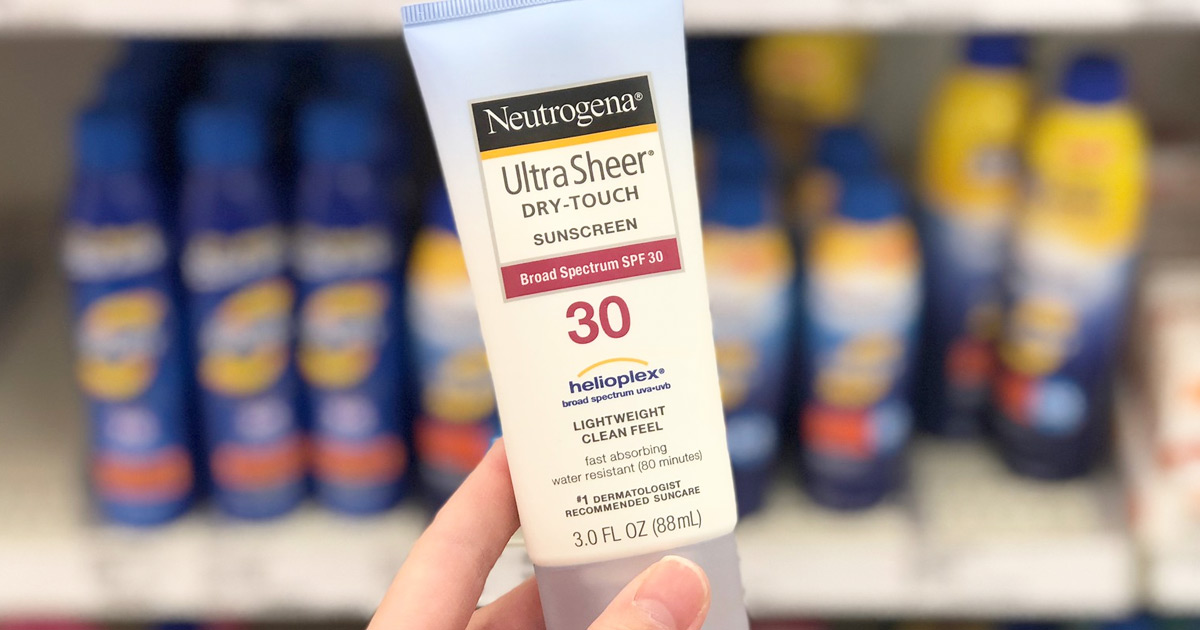 person holding up white and blue bottle of neutrogena sunscreen