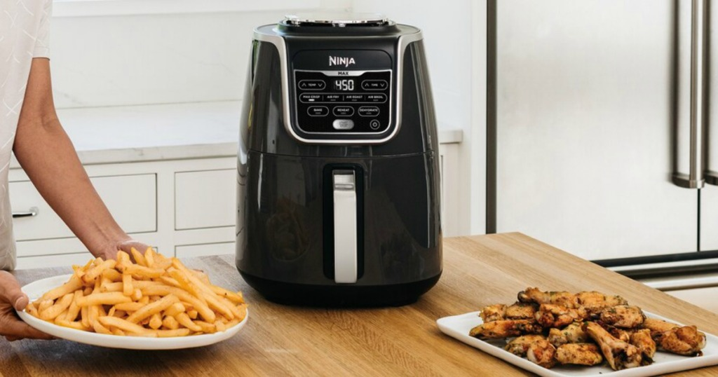 Woman grabbing a plate of fried foods near an air fryer on the counter