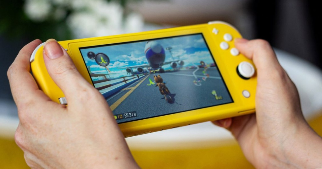 hands playing on yellow gaming console