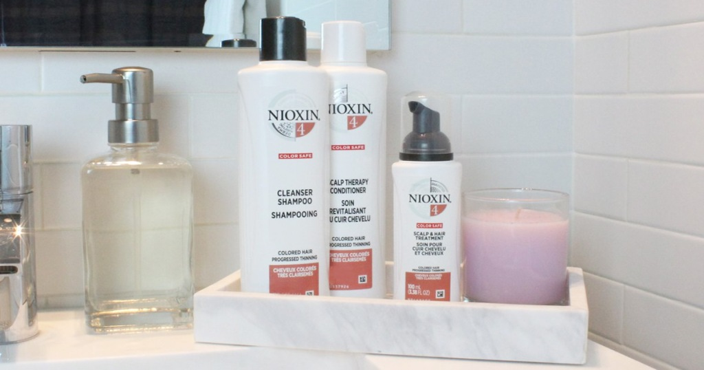 nioxin shampoo and conditioner bottles sitting in marble tray on bathroom counter
