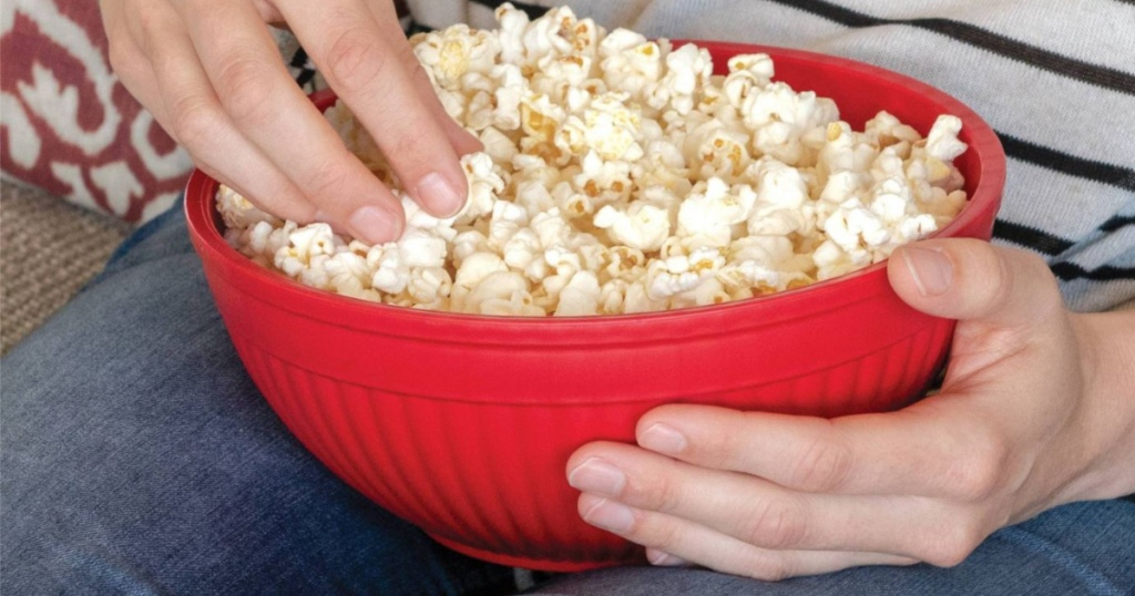 hands picking popcorn out of red bowl on lap