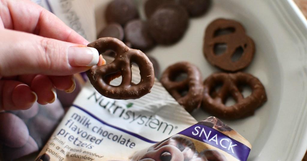 hand holding chocolate pretzels