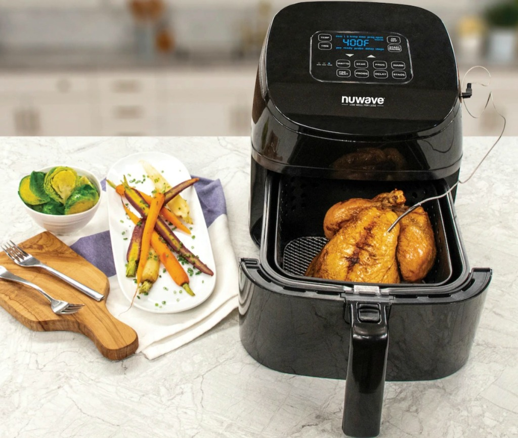 Large air fryer on counter with basket open and fried foods inside