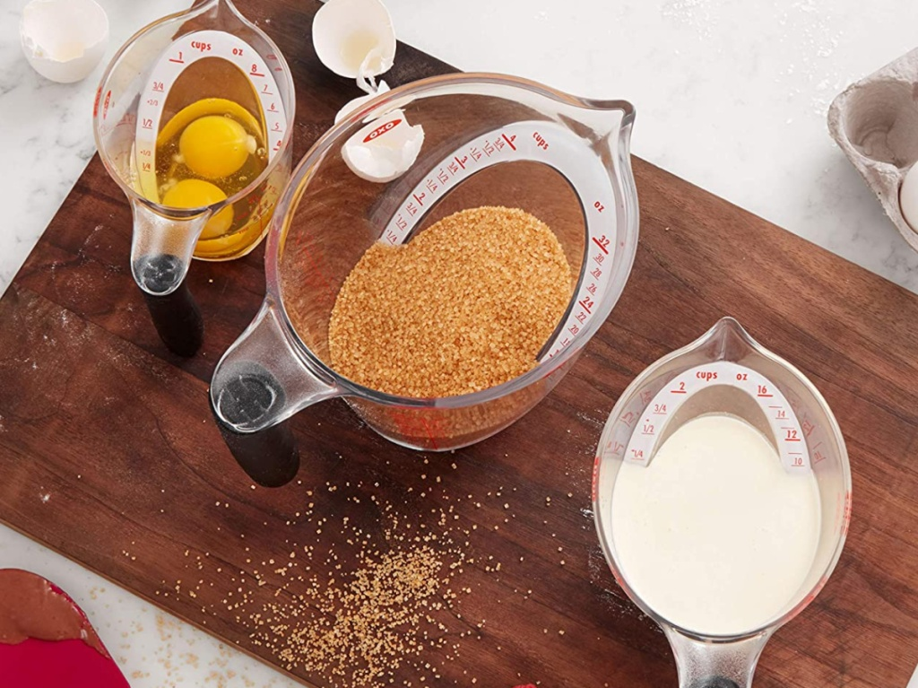 various sizes measuring cups on cutting board, filled with food items