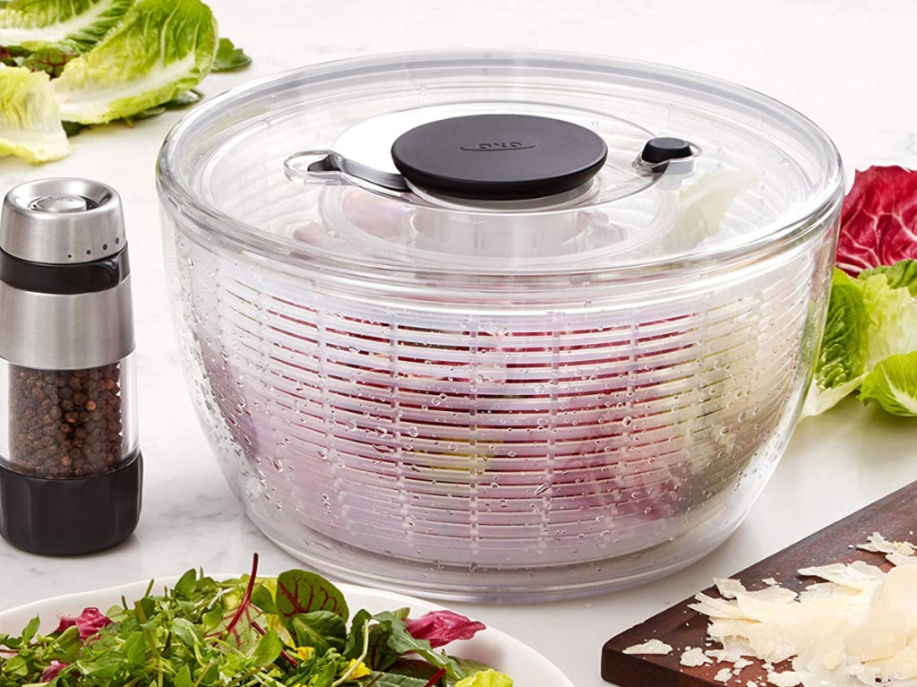 large clear salad spinner on table with pepper, salad on plate, and cutting board with ingredients