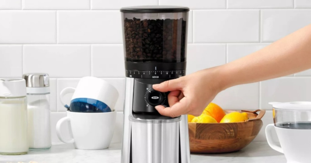 woman turning knob on a coffee grinder