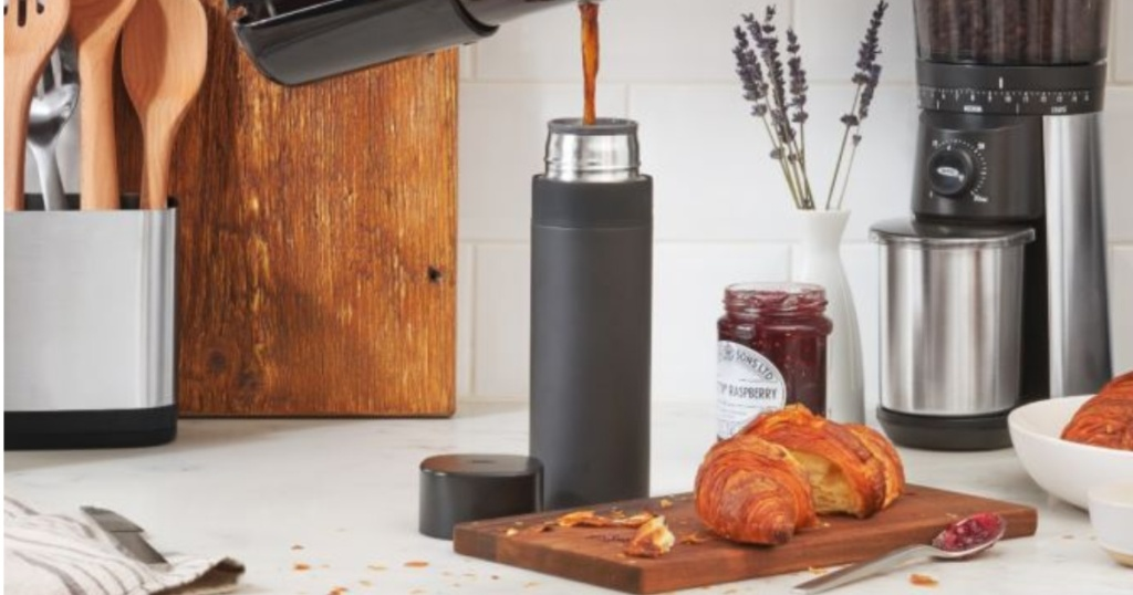 Coffee being poured into a black thermos with cutting board and bread on counter top
