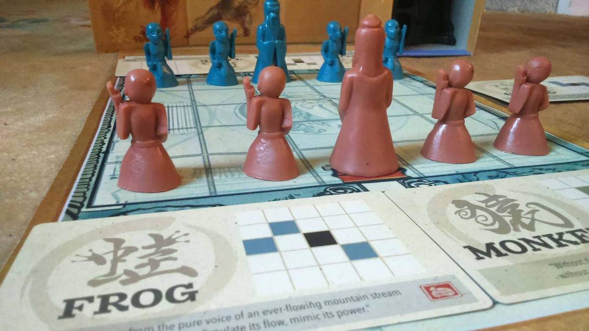 Onitama game board with pieces on it