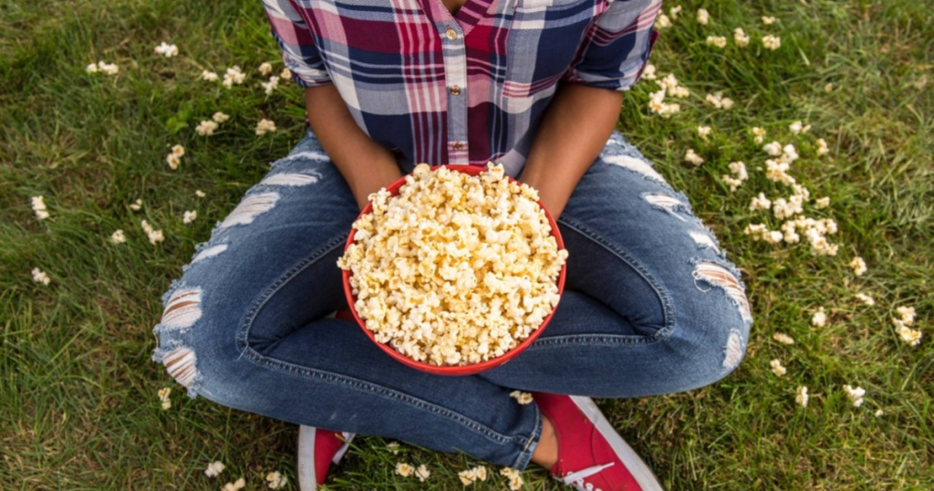 girl sitting with legs crossed holding red bowl of popcorn