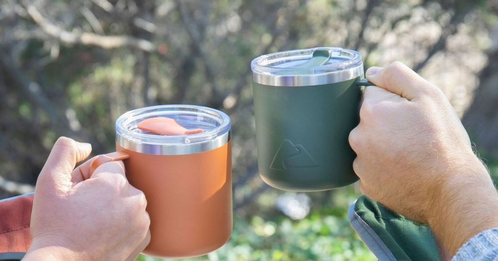 two hands each holding an insulated stainless steel mug