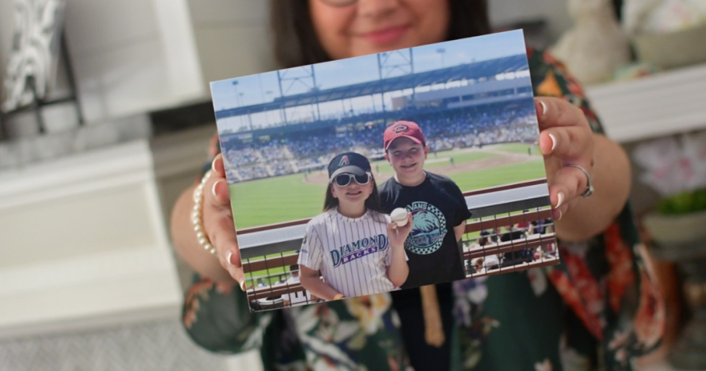 woman holding photo of children at baseball game