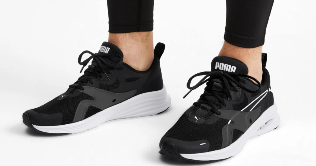 man wearing black and white running shoes