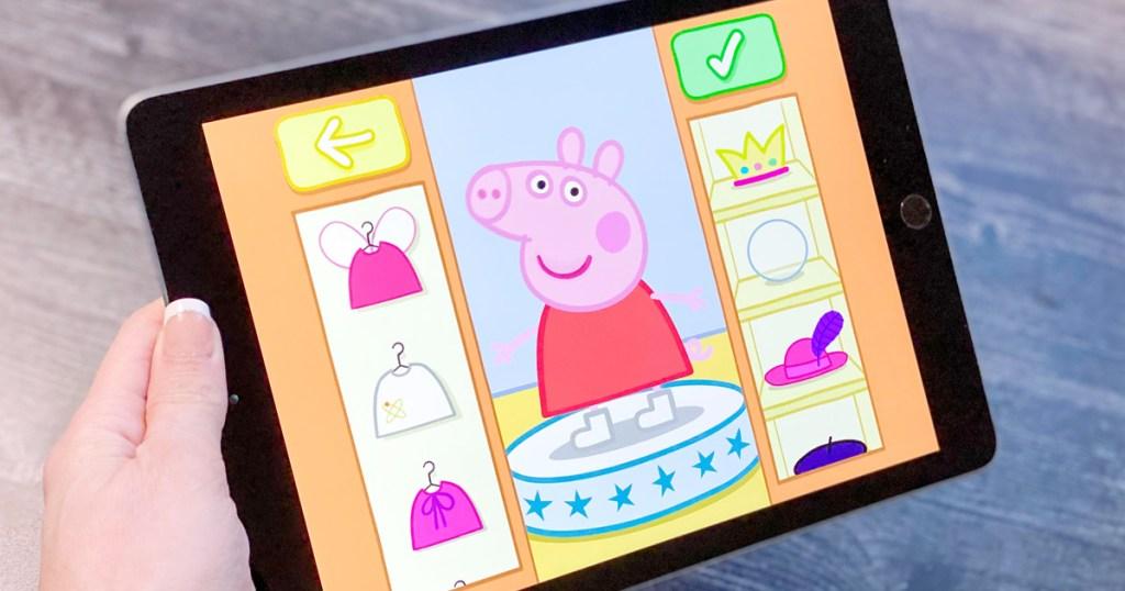 woman holding black ipad playing app dressing up peppa pig