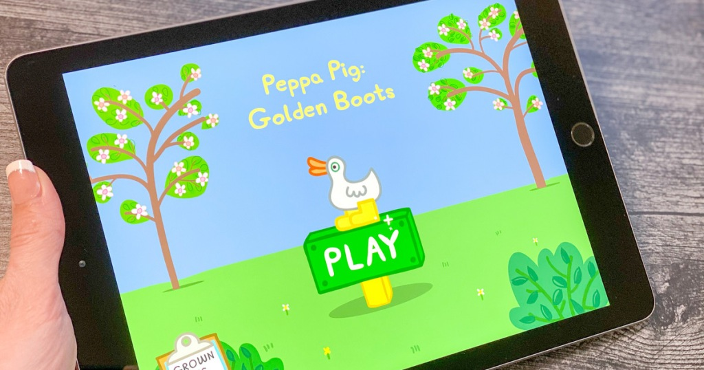 woman holding black ipad playing peppa pig golden boots game
