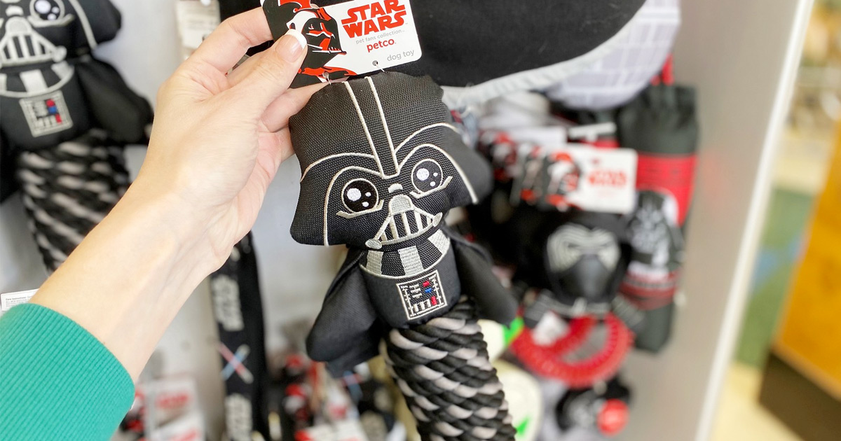 woman holding up darth vader shaped dog rope toy