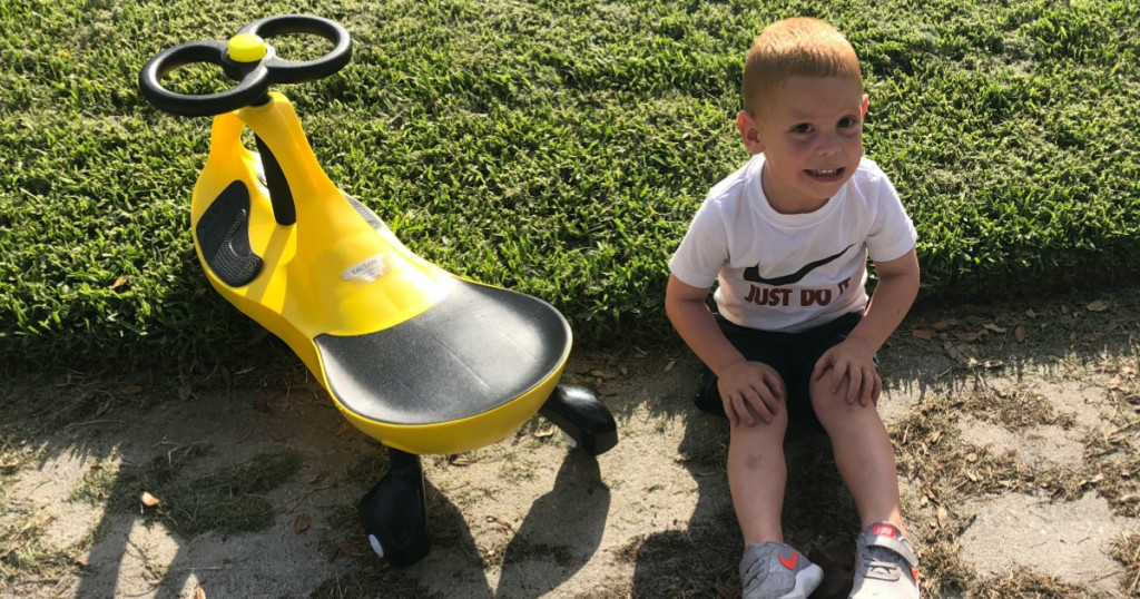 boy sitting on grass next to a yellow and black swing car