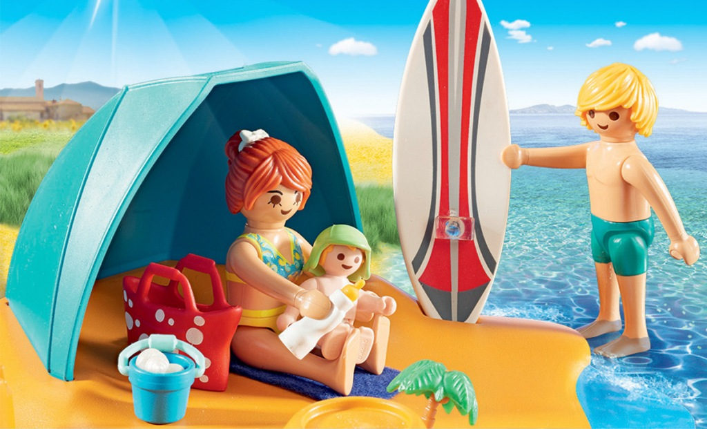 family of playmobil characters on beach with surf board and shade tent