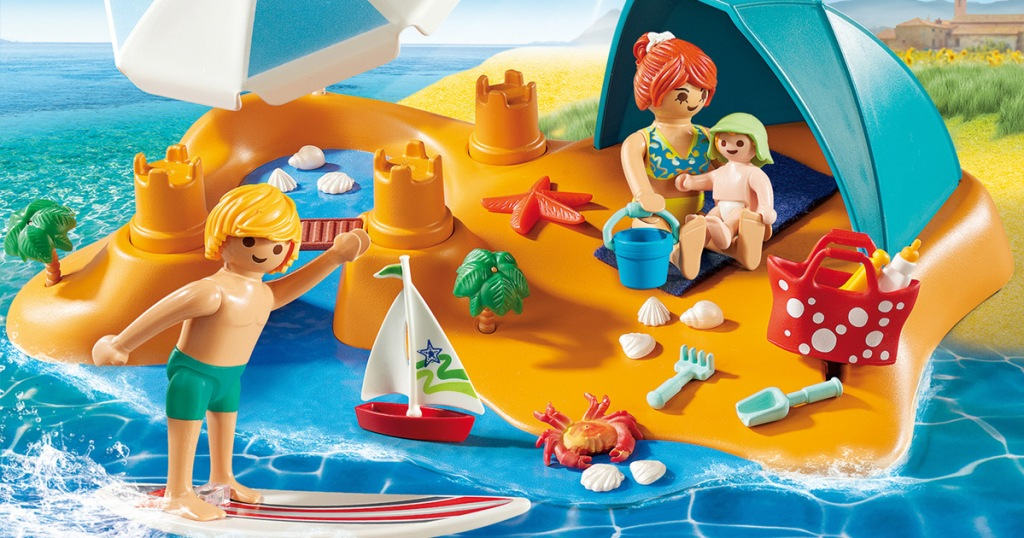 playmobil family on beach with beach toys and sand castles, and man surfing in water