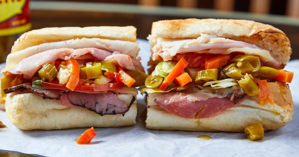 sandwich with meat and veggies cut in half on parchment paper