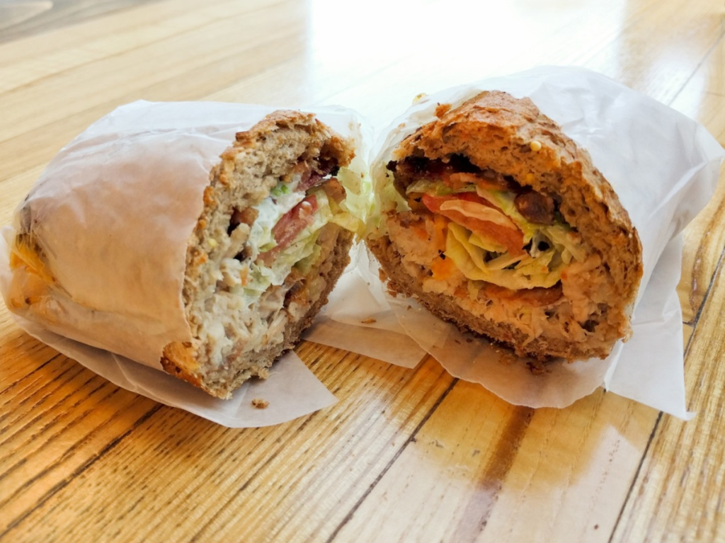 wrapped sandwich with meat and veggies cut in half on table