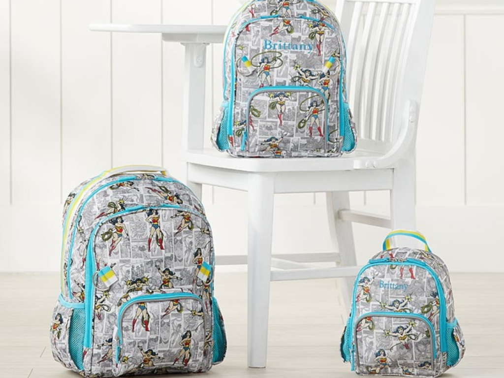 3 pottery barn wonder woman backpacks sitting next to each other and a white chair
